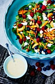 A colorful salad with nuts and berries