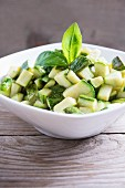 Diced zucchini in a bowl on a wood table