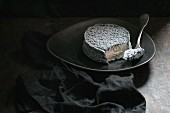 Goat cheese with gray mold with fork on dark plate over black background