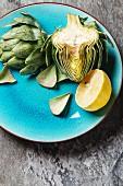 Babyartischocke und Zitrone auf türkisem Teller