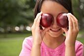 Mädchen hält sich zwei Pflaumen vor die Augen