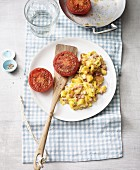 Bacon and scrambled eggs with diced bread and fried tomatoes
