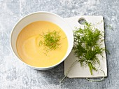 A bowl of potato and carrot soup with fresh dill