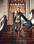 Blonde Frau in Paillettenkleid, gemustertem Seidenmantel und roten Pumps geht Treppe hinunter