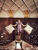 Blonde Frau in lila Satinkleid mit Volantsaum, Statementkette und Loafer steht auf Stuhl und schüttelt Daunenkissen