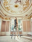 Blonde Frau in geblümtem Chiffonkleid und goldenen Schnürpumps mit langem geflochtenem Zopf auf Leiter