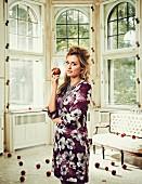 Blonde Frau in Shiftkleid mit Blumenprint und Statementkette hält einen Apfel