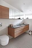 Helles Bad mit weißen Fliesen und eingebauten Bademöbeln