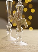 A candlestick holder with a golden reindeer figure on a festively set table