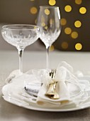 A Christmas table setting with a white bow and crystal glasses