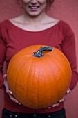 A woman holding a giant pumpkin
