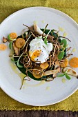 A poached egg on fried leeks with spinach puree, herbs, kumquats and borage shoots