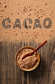 Cocoa powder in a bowl and spilled on a wooden background with the word 'cacao'
