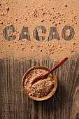 Kakaopulver im Schälchen und auf Holzuntergrund mit Schrift Cacao