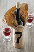 A bottle of red wine in a paper bag with a question mark