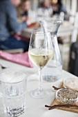 Weissweinglas, Wasser, Salz und Pfeffer auf Tisch im Restaurant