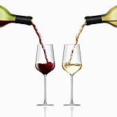 Red and white wine being poured into wine glasses side by side