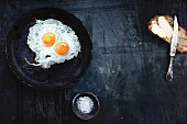 Fried eggs cooking in frying pan with bread and butter ready