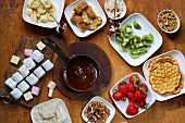 Chocolate fondue with fruit, waffles, marshmallows, biscotti and nuts