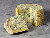 A whole stilton cheese with a quarter cut out shown on a grey background