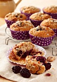 Blackberry and honey oat muffins, one shown broken open in front with blackberries, others on cooling rack