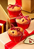 Three Festive cranberry and marzipan muffins tied with ribbon sitting on wrapped gifts in a Christmas setting