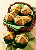 Several Easter muffins with marzipan crosses in a basket and on a napkin sitting on a gingham cloth