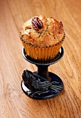 A Pecan and Maple (syrup) muffin in a gold muffin case on a small blue stand with a ceramic bird all sitting on a wooden surface