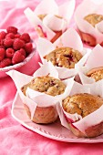 Raspberry cranachan muffins in while cupcake cases on a pink plate