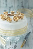 A white festive cake with gold roses and decorative ribbon