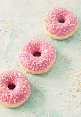 Three pink donuts with sugar sprinkles