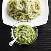 Glasschälchen mit Pesto, im Hintergrund Spaghetti mit Pesto