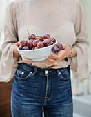 Frau hält Schale mit Weintrauben
