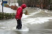 Man walking through flood waters