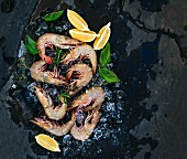 Fresh uncooked shrimps with lemon, herbs and spices on chipped ice over dark slate stone backdrop