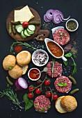 Zutaten für Burger: Brötchen, Patties, Gemüse und Tomatensauce