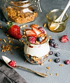 Yogurt oat granola with fresh berries, nuts, honey and mint leaves in glass jar on grey concrete textured backdrop