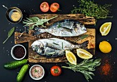 Fresh uncooked dorado or sea bream fish with lemon, herbs, oil, vegetables and spices on rustic wooden board