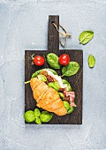 Croissant sandwich with Prosciutto di Parma, sun dried tomatoes, fresh spinach and basil