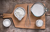 White frosting and ingredients on light cutting board and light rustic wood surface