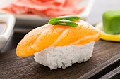 Nigiri sushi with salmon on a wooden plate