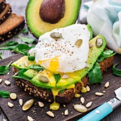 Avocado sandwich with arugula, seeds and poached egg
