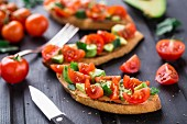 Bruschetta with tomato, avocado and herbs on a black wooden table