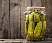 Jar of homemade pickles on a rustic wooden board