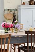 Alter Tisch gedeckt mit frischen Blumen in Einmachgläsern