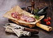 Rohes Steak mit Gewürzen, daneben Fleischgabel