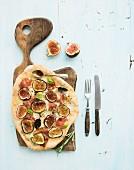 Rustic homemade pizza with figs, prosciutto and mozzarella cheese on dark wooden serving board
