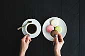 Macaron cookies, cup of espresso and ladie s hands over black wooden backdrop