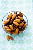 Almonds and raisins in a glass bowl