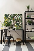 Arbeitsplatz mit schwarzen Möbeln und Pinnwand mit Dschungelprint